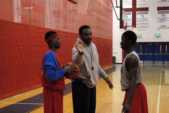 T.C. Williams head boys' basketball coach Julian King talks to Warren Smith, left, and Darius Holland during practice on Monday.