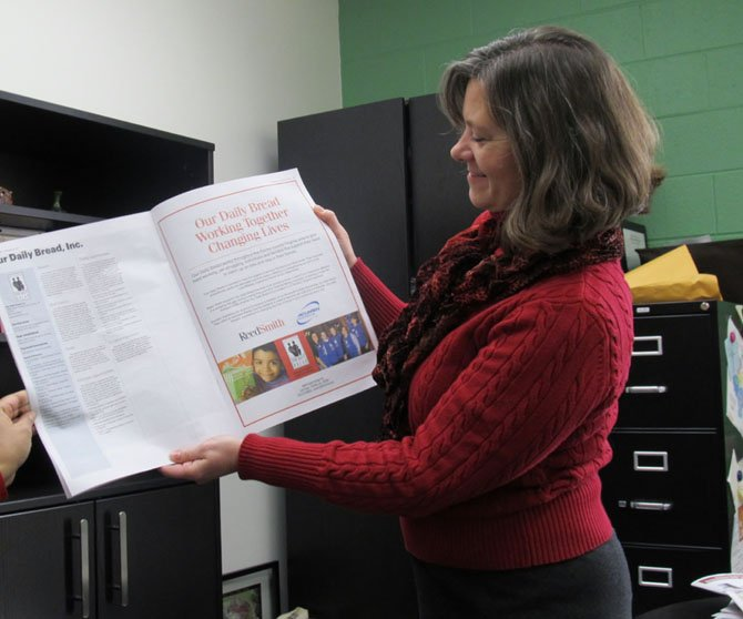 Lisa Whetzel, executive director of Our Daily Bread, holds up an advertisement of the organization that encouraged donations.