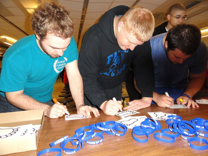 Signing their anti-bullying footprints are (from left) Andrew Orvedahl, Alex Brunner and Kyle Wilkinson.