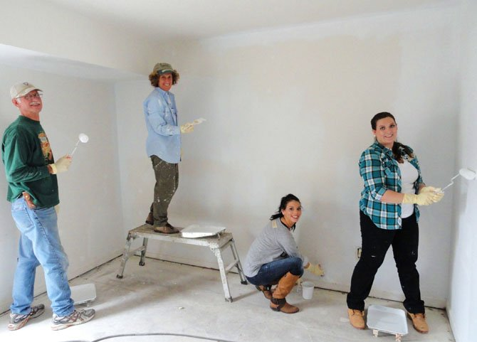 Painting the living room are (from left) sandlot volunteers Craig Taylor and Laurie Corkey and FM Global's Mercedes Powers and Dallas Gage.