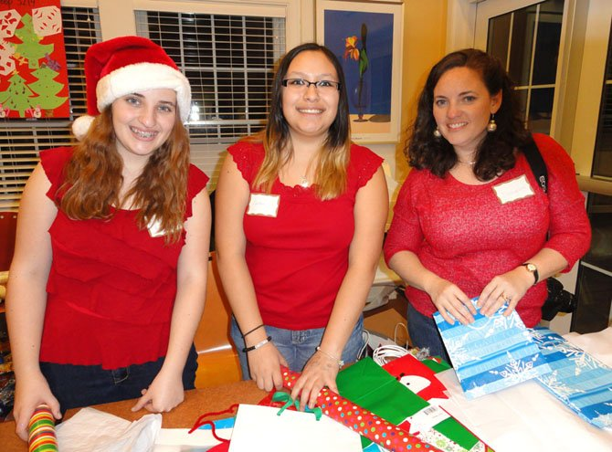 Wrapping children's gifts at the family shelter are (from left) Lake Braddock sophomore Liz Barr and Robinson sophomore Carolina Gonzalez, both of Girl Scout Troop 870 of Burke, plus Liz's mom, Evangeline Barr.