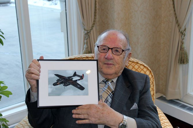 Ray Gilbert sits at the Fairfax near Fort Belvoir with a picture of a P-61, on which he served as a radar operator in World War II.