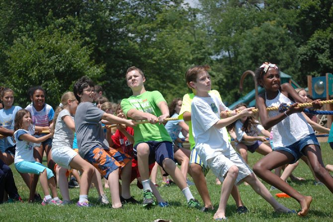 Students at the Summer at Norwood camp play tug-of-war. Experts say summer camps should offer opportunities for play, socialization and rest.