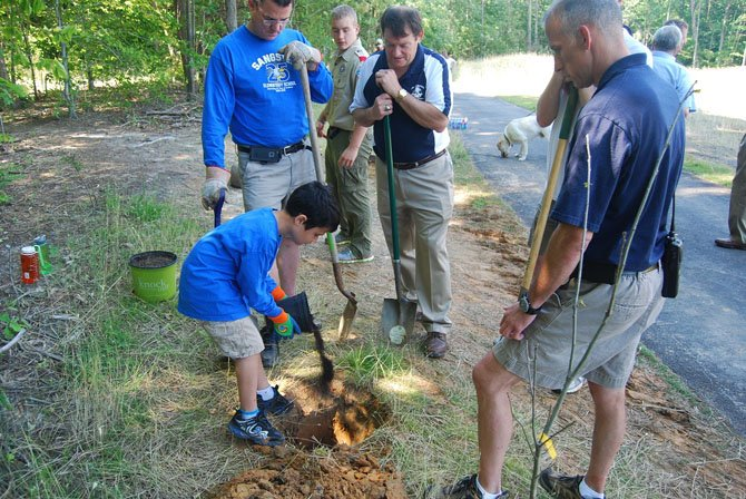 "Virginia Delegate Dave Albo, Springfield Supervisor Pat Herrity and a representative from the Fairfax County Parks Authority help a volunteer from Boy Scouts from Troop 1140 at Burke Lake Park. The ""1,000 Trees in 1,000 Days"" program, launched by the 95 Express Lanes project private partners Transurban and Fluor in 2012, aims to restore greenery to areas that lost trees during construction of the express lanes."