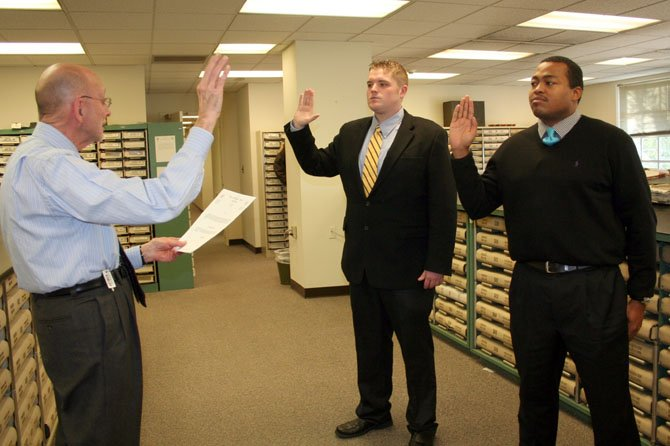 Two new deputies have joined the Alexandria Sheriff's Office. On Thursday, Jan. 16, the recruits received their badges and credentials and then were sworn in at the Alexandria Courthouse by Clerk of the Circuit Court Edward Semonian. Deputy Samuel Clark (right) and Deputy Phillip Leger(center) will complete several weeks of training at the William G. Truesdale Adult Detention Center before attending the Northern Virginia Criminal Justice Training Academy later this year.