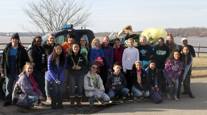 Volunteers from South County Middle School, including many members of Cadet Girl Scout Troop 340 of Lorton, pose in front of the trash they collected at Mason Neck State Park.