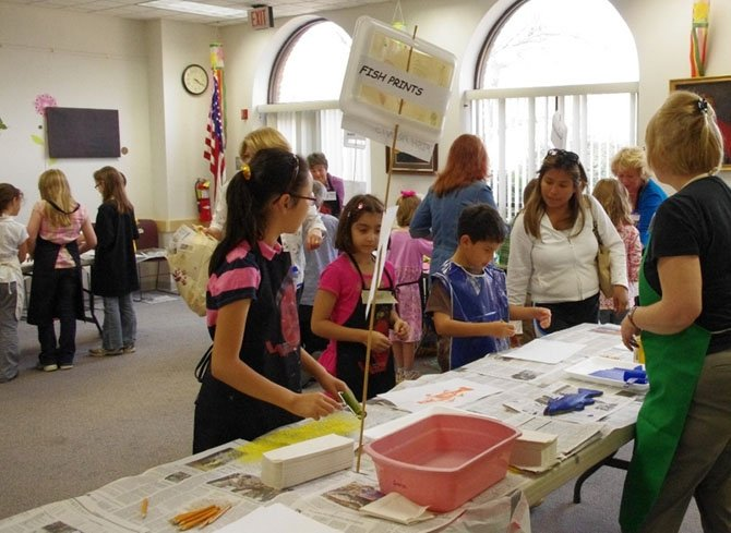 Artists from the Vienna Arts Society volunteer with children at the printmaking workshop it sponsors in cooperation with Patrick Henry Library. The next free workshop is Tuesday, March 25.