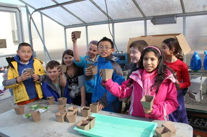 Churchill Road fourth graders plant parsley to sell at their farmer's market in June. From left: Oliver Tu, Ryan Campbell, Marin Heberlig, Amelia Rewis, Andrew Zhou, Christopher Tillotson, Riya Dev and Anjali Donnelly.