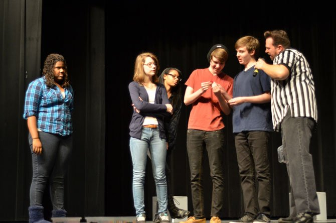The Mt. Vernon Blue improv team learn what their scene will cover. From the left, Jordyn Stewart, Erin Harroun, Chloe Colbert, Austin Shores, and Tyler Shores, and event referee Scott D. Pafumi.