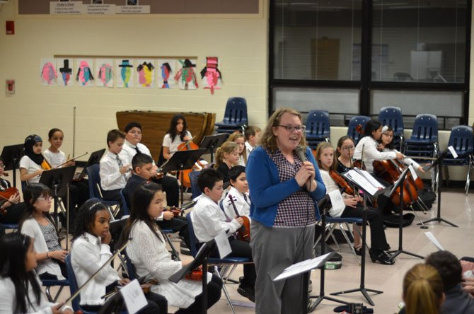 Music teacher Allison Devereux speaks to parents and audience at Dranesville Elementary School during the February evening Strings Concert.
