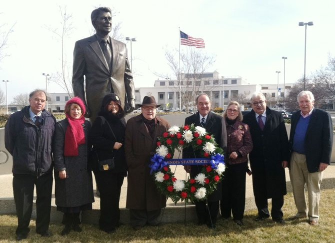 Metropolitan Washington Airports Authority vice president and airport manager Paul Malandrino (fourth from right) joins members of the DC Chapter of the Illinois State Society at a wreath-laying ceremony Feb. 6 at the airport's statue of Ronald Reagan to commemorate the former president's 103rd birthday. From are Jack Ames, Fran Griffith, Cheryl Rhoads, former Illinois state senator Mark Rhoads, Malandrino, Jeanne Jacob, Larry Krakover and Gerry Frank.