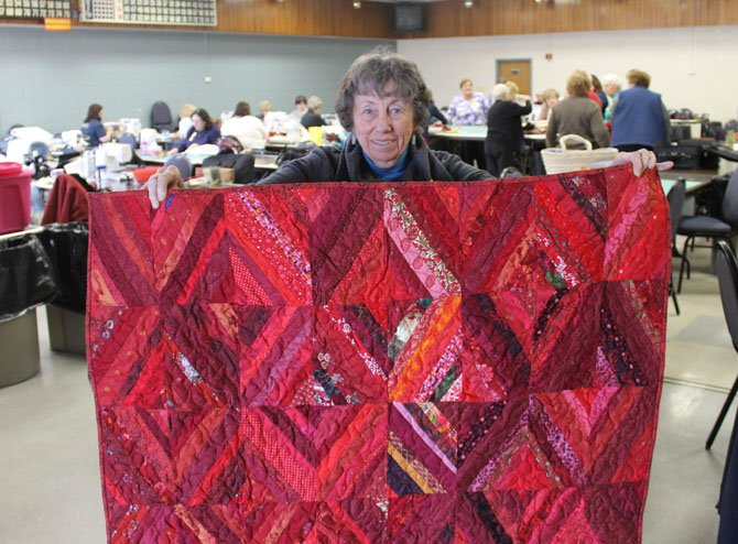 Fairfax Station resident Joan McGowan presents her quilt for the Wounded Warriors project at a Springfield Quilters' Unlimited workshop. McGowan has held membership in Springfield Quilters' Unlimited longer than any other member in the group.