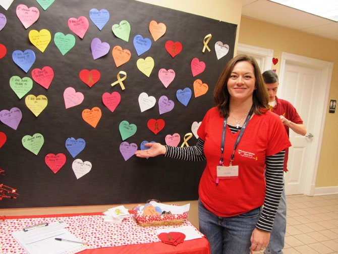 Laurie Florence, a member of the Friends of Sadie Planning Committee, displays the colorful paper hearts blood donors were given at the blood drive to write down the reasons why they were giving blood.