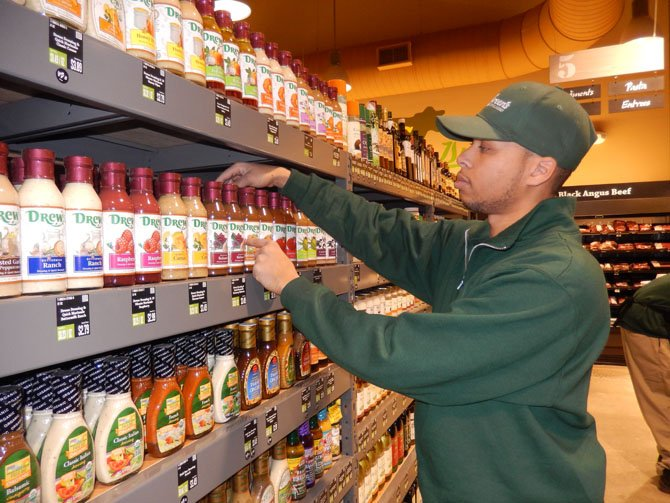 Grocery Manager Alonzo Jordan checks the price tags on the salad dressings.