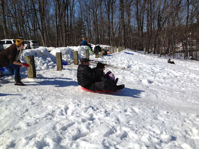 Families spend the snow day on Friday afternoon sledding on the hill beside the Children's House Montessori School on Wiehle Avenue in Reston.
