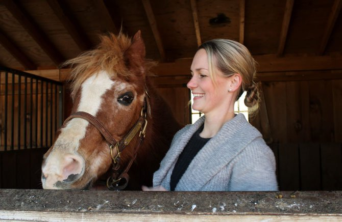 Peaches, a horse of the Northern Virginia Therapeutic Riding Program, stands with Kelsey Gallagher, NVTRP interim executive director.
