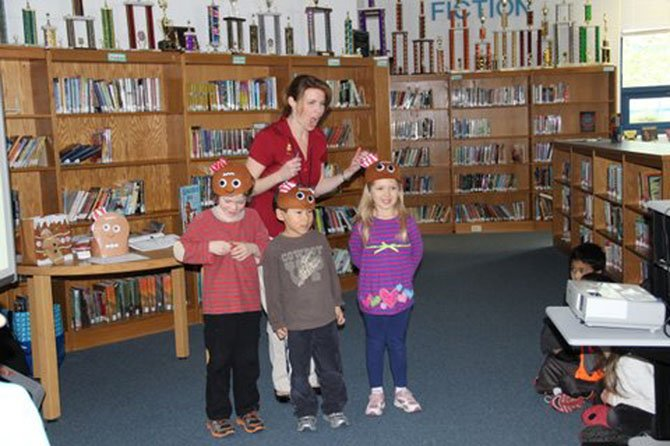 "Churchill Road kindergarteners Zach Smith, Andrew Park and Kara Dinker were happy with their response on the ""Gingerbread Man Quiz Show,"" presented by visiting author Laura Murray."
