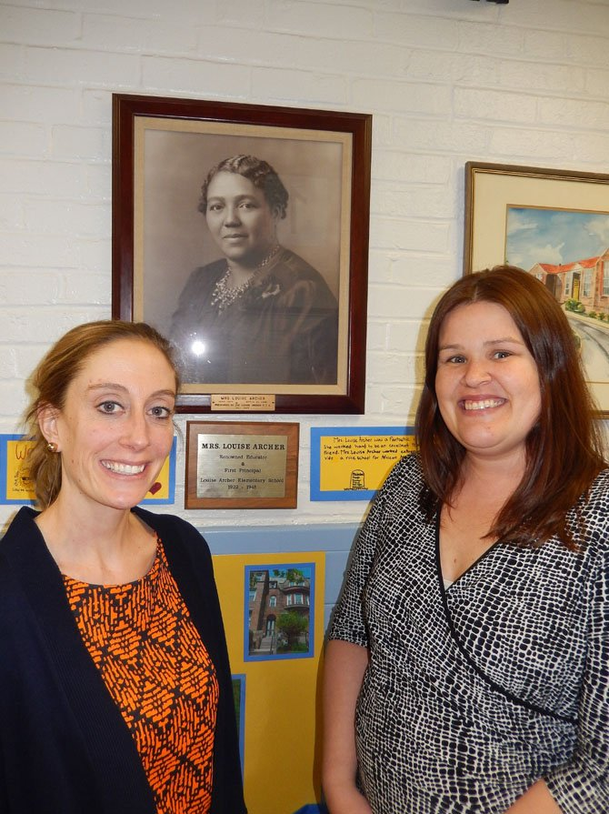 (From left) are teachers Lauren Wagner and Kris Beurmann under a portrait of Louise Archer.