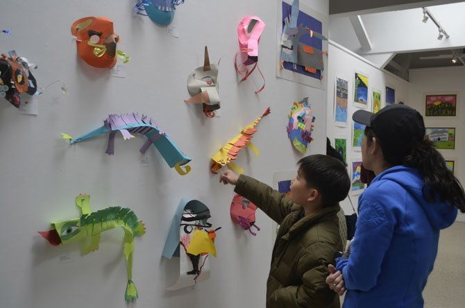 Youth art exhibition visitors admire a wall lined with colorful paper figures.