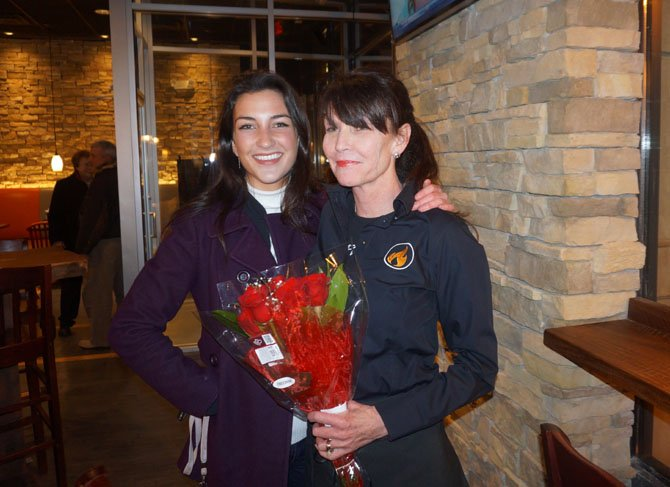 Donna Anderson, right, gets flowers from daughter Dakota at the Feb. 27 opening of Sweet Fire Donna's BBQ restaurant in the Carlyle neighborhood of Alexandria.