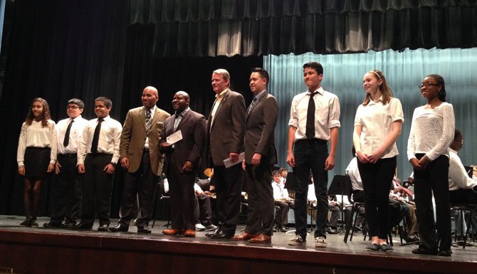 First Night board member Kerry Donley, fifth from right, poses for a photo with ACPS band and orchestra members after presenting a check for $3,000 to support the music programs of Francis Hammond and George Washington Middle schools and T.C. Williams High School.
