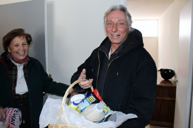 David Vernon recently moved into the FACETS TRIUMPH II Housing program, which houses individuals who were previously chronically homeless. In this picture, Elsbeth Hoff of the Gracing Spaces program greets Vernon with a donation basket at the housewarming celebration welcoming 18 previously homeless clients into their homes.