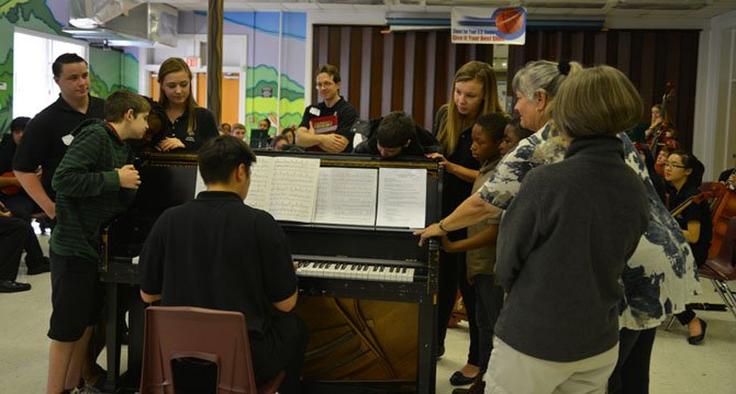 Cherokee students and teachers touch the piano to feel the sound vibrations while Langley HS sophomore Theron Masters plays a familiar tune. Langley HS Orchestra conductor Dr. Scott McCormick and his students enjoy the moment.