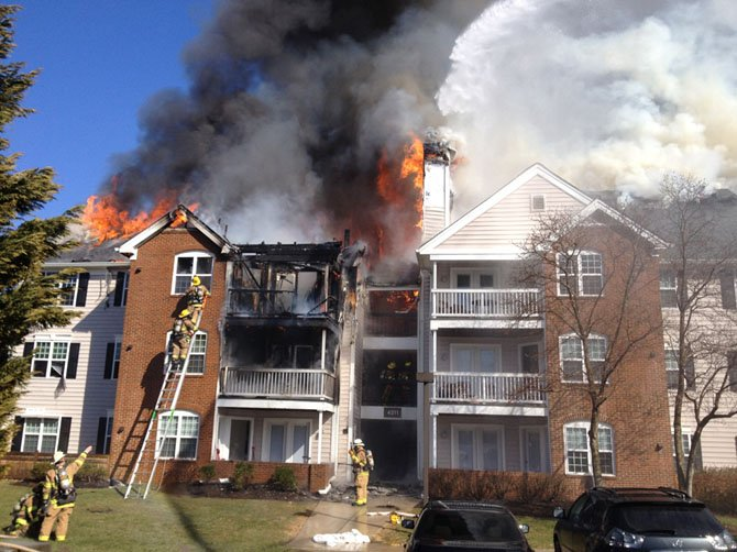 City of Fairfax firefighters rescue occupants and attack the blaze as smoke and fire pour out of the building.