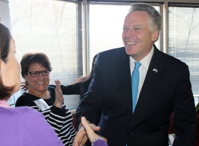 Gov. Terry McAuliffe greets an attendee of a Medicaid expansion roundtable discussion at Alexandria Neighborhood Health Services in Arlington on March 20.