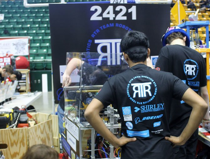 Members of RTR Team Robotics Team 2421, which includes students from Springfield, Burke and Fairfax, examine their robot at the FIRST Robotics Competition on March 28. The team will also be competing at the Chesapeake Regional competition in Maryland from April 3-5.