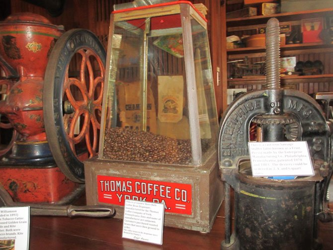 Coffee beans were scooped from this cast iron and glass storage container into a manual coffee grinder.