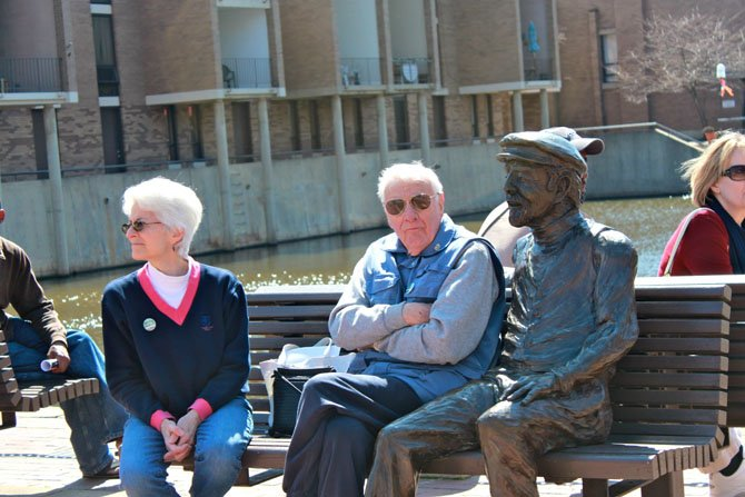 From left, Reston residents Susan Aylward and Bill Aylward sit next to Robert Simon's statue before the Founder's Day festivities Saturday.