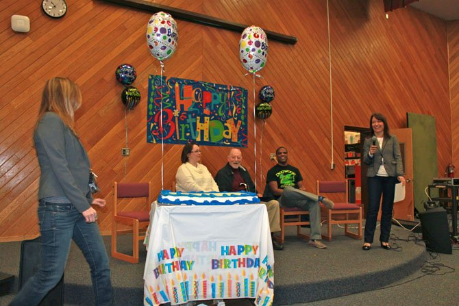 Langston Hughes Middle School Principal Aimee Monticchio presents Robert Simon with a cake to celebrate his 100th birthday.