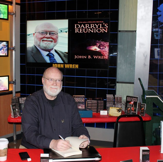 "John B. Wren, who lives on the outskirts of Burke in Bonnie Brae, signs a copy of his book ""Darryl's Reunion"" at a book fair for crime writers at the National Crime and Punishment Museum in Washington, D.C. on April 12."