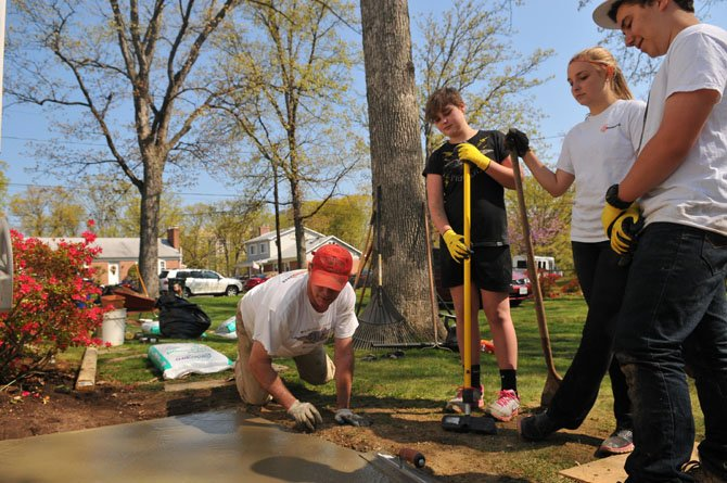 Beck Moniz, Kate and Emma Sapp listen and watch as a volunteer smooths out a freshly poured concrete slab.