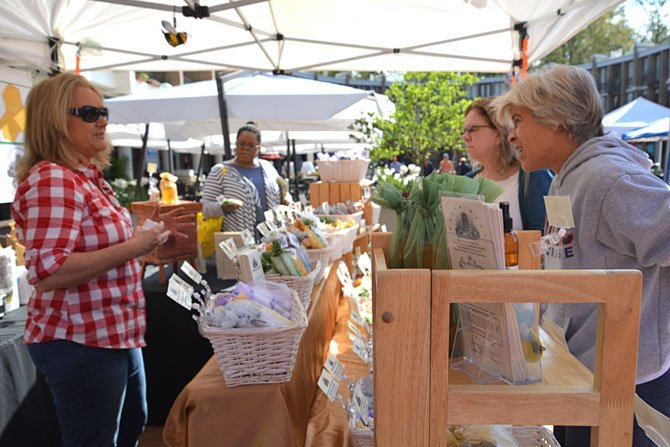 "The Open Air Market in the Lake Anne Plaza is also open for business. Featuring artisans, global imports and health products like the many ""Beehive Remedy"" offerings of InterNutrionals, LLC of Oakton. Michele Bucharnikov had her hands full with customers a plenty."
