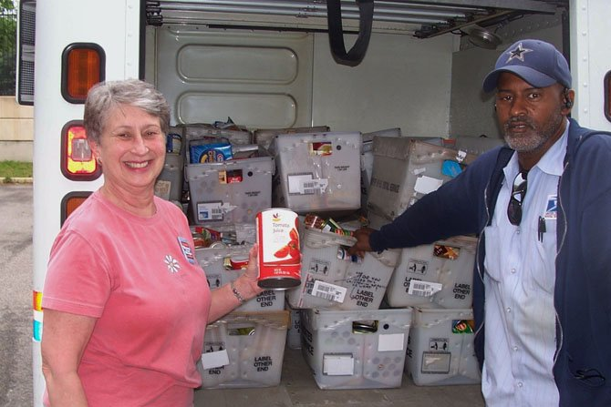 Parkfairfax Letter carrier Dwayne Chittum, right, is joined by Beth Campbell of ALIVE! during last year's Stamp Out Hunger food drive. This year's food drive collection will take place on Saturday, May 10.