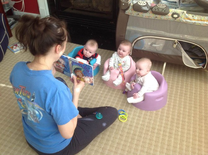 Mommy Margie Morgan reading a story to her triplets.