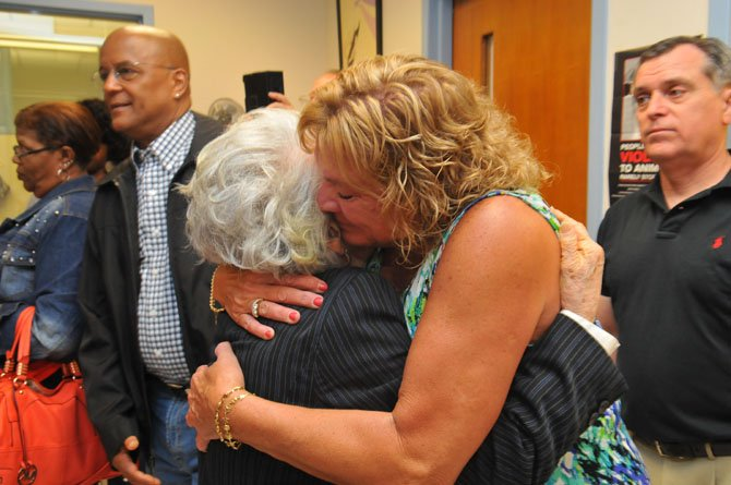 Longtime friend of the family Marjorie Harris gives Virginia Smith's daughter Renee a hug at the conclusion of the ceremony.