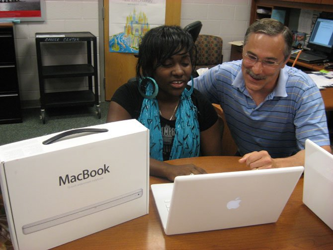 Laptops for Success program founder Marie Assir and former Principal Bruce Butler in a photo from 2009, play with the newest Macbook model.