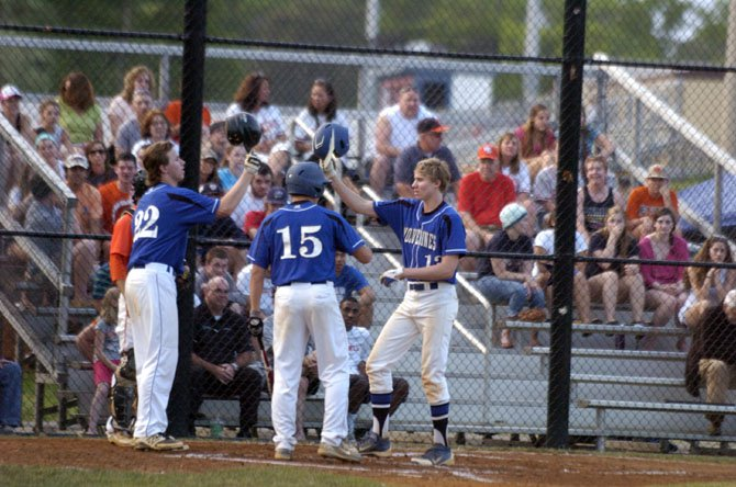 West Potomac sophomore Jamie Sara, right, is greeted at home plate by teammates Billy Lescher (22) and Rocky Iboleon (15) after hitting a two-run home run in the first inning against West Springfield on May 13.