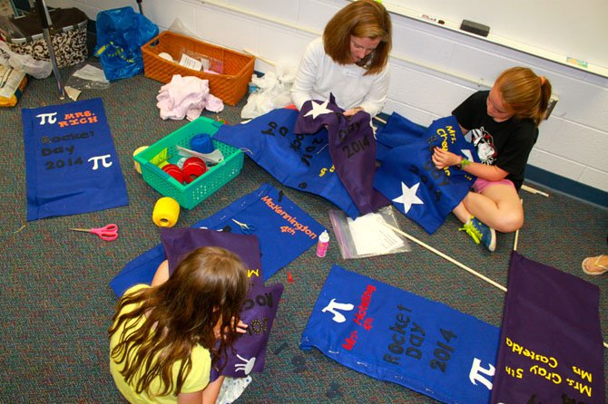 Left to right, top to bottom, parent Amy Augenblick works with fifth grade student Elizabeth Augenblick and fourth grade student Sophia Fox to create banners for Rocket Days.