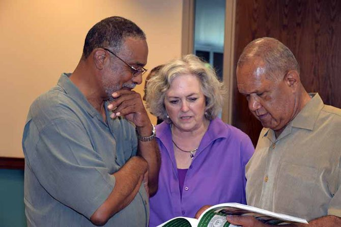 "At a reception at Wakefield on May 22, Clayton Powell, Conchita Mitchell and Larry Randall look at ""Integration of Wakefield Highs School"" that Mitchell co-authored."