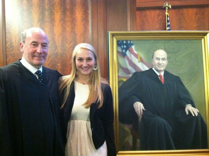 "Judge Roger W. Titus poses with his granddaughter, Emily Titus, at the May 8 portrait ceremony at the U.S. District Court for the District of Maryland. Emily was among the more than 100 guests who witnessed ""the hanging of the judge."""