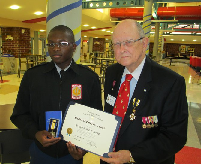Cadet 1LT Derrick Beck, left, of T.C. Williams High School, receives a Bronze ROTC medal May 14 from Jack Pitzer of the George Washington Chapter of the Sons of the American Revolution.