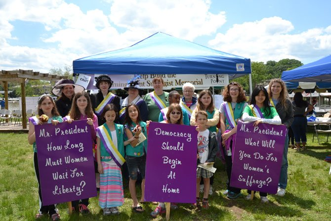 Pictured in the group photo of Troop 707 and women dressed as suffragists are, from left:  Back row: (Suffragists) Julianne Smith, Sue MacIntyre, Lynne Dudurich, (scout leader) Karan Wright, Savannah Dingle, Sally Miller, Kathryn Wingard, Grace Strong, Maryn Ballard, and (scout leader) Erika Malos-Keil.  Front row: Annette Wright, Alexandria Strong, Lily Miller, Kiera Gilbert, Ellen Keil, and Henry Keil.