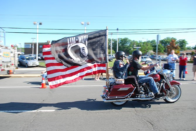 A motorcycle of the Ride of the Patriots blazes by and parades both an American Flag and a Prisoners of War and Missing in Action flag Sunday, May 25.