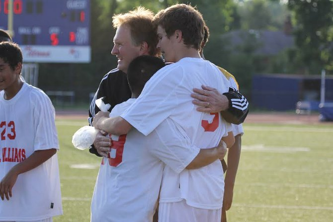 T.C. Williams boys' soccer coach Martin Nickley celebrates with his players following a 2-1 overtime victory against McLean in the 6A North region quarterfinals on May 30.
