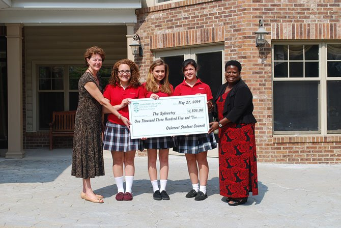 Oakcrest senior council presents the Sylvestery with a $1300 check. From left: Kathleen Martin, CEO of Vinson Hall, Cathryn Grace Sreco, Gianna Ridout and Alex Aguilar and Robin Walker, clinical manager of the Sylvestery