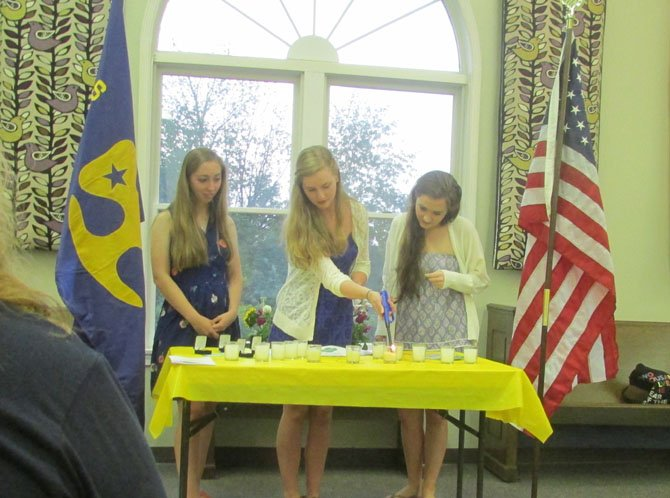From left, Rachel Zmuda, Caitlin Dalrymple, and Maddie Navin all of Troop 1057, of Great Falls, are honored on May 27, 2014 for completing their Girl Scout Gold Awards. Pictured here, they are reciting the Girl Scout Promise and Law during a candle lighting ceremony.